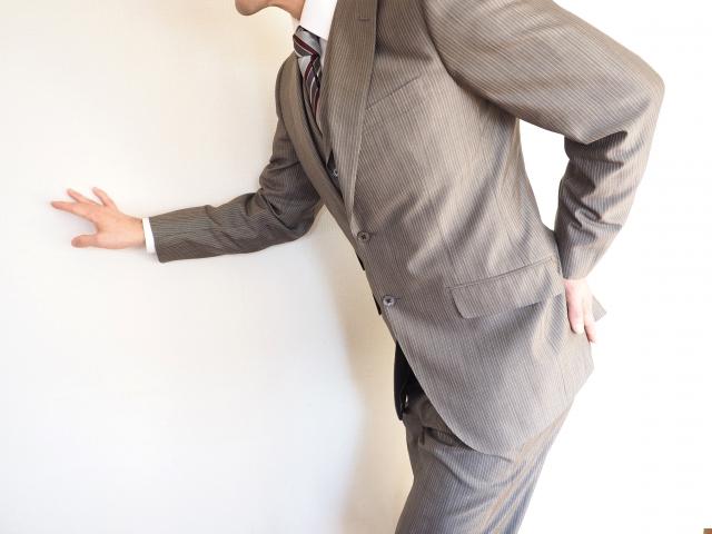 腰痛克服 腰をおさえるビジネスマン